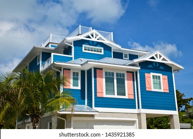 Large Beach House painted in dark blue with white trim and coral shutters. House has roof deck, garage and beautiful landscaping including Palm Trees