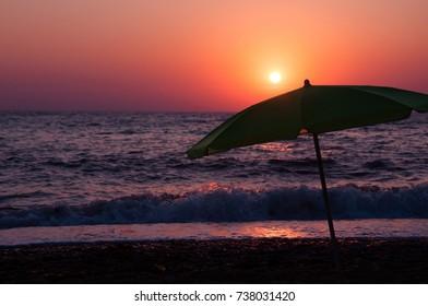 A large beach umbrella on a sunset background. The shore of the sea in Lyubimovka. Sevastopol. Crimea.