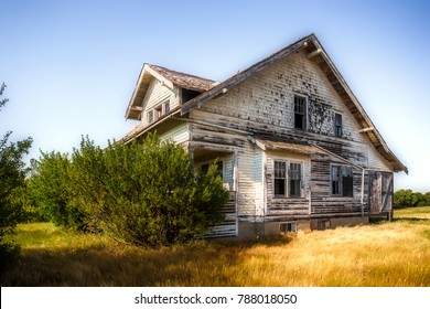 A large beautiful wooden two story abandoned farm house with peeling paint and broken windows in a rural summer countryside