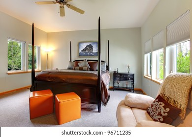 Large bedroom with five windows and black post bed with brown bedding. Modern and classic comfortable design.