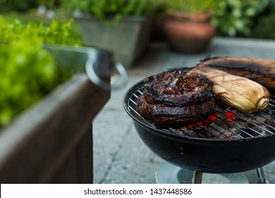 A large beef brisket and corn in the husk being barbequed on a small charcoal hibachi grill with glowing coals underneath.