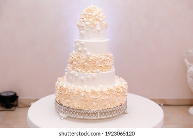 A large beige five-tiered wedding cake with delicate cream and whipped cream on a white table in a restaurant. Dessert for guests