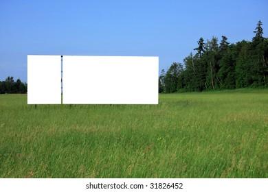 Large bill board in a field along the highway.