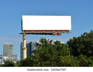 Large Billboard in the city. Green trees, modern buildings, blue sky. Outdoor advertising in South Florida.
