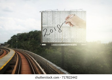 A large billboard with a hand writing the year 2018 along an elevated train track, for the concept: Arriving into New Year 2018.
