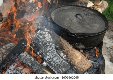 Large Black 16 Sixteen Inch Lodge Camp Dutch oven sits in the hot fire and cooking a meal