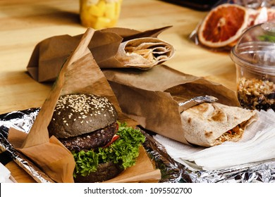 A large black hamburger with pork chop and lettuce, pita bread with vegetables and a glass with granola on the wooden table. A hearty delicious breakfast. Street food.