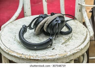 Large black headphones on older white chair