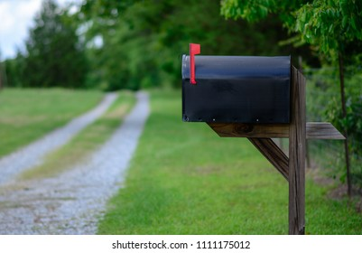 A large black metal mailbox along a quiet country road
