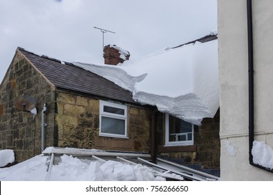 Large blanket of snow slowly sliding of a house roof. Part of roof clear from snow sliding off and crashing through conservatory below.