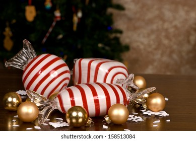 Large Blown Glass Peppermint Candy, Small Christmas Bulbs and snowflakes on a wooden table top in front of a Christmas tree.