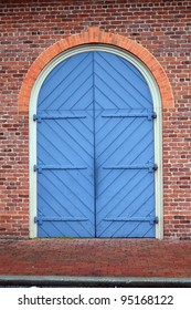 Large Blue Carriage Door in a Red Brick Wall