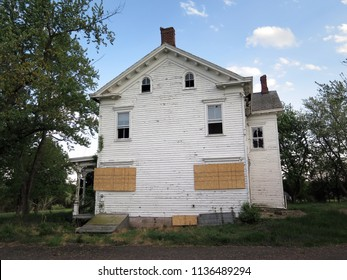 Large boarded up abandoned farmhouse. Low angle.