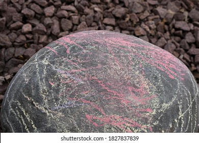 Large bolder covered in sidewalk chalk of different colors with background of red river rock out of focus