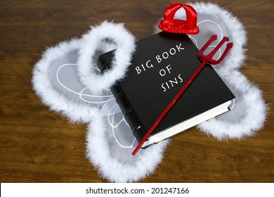 Large book labeled Big Book Of Sins on desktop with angel wings and halo, devil horns and pitch fork