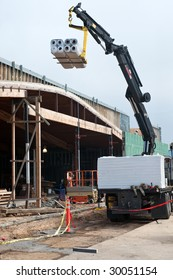 A large boom lifting a pallet of roofing material