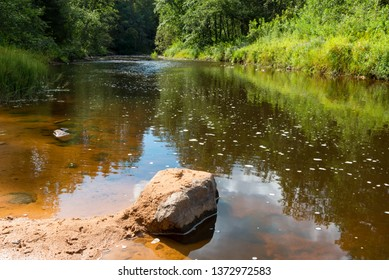 A large boulder lies in the water of the Polomet River, Novgorod Region, Russia