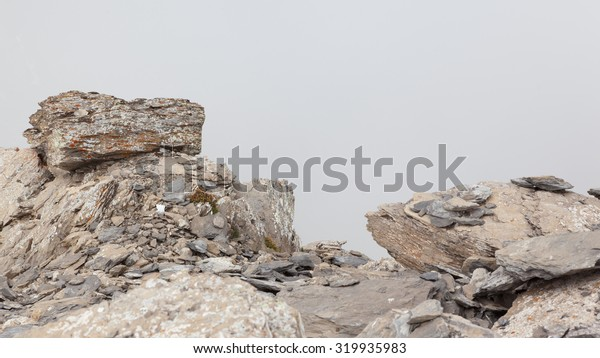 Large boulders in fog on a Swiss mountain summit