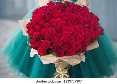 Large bouquet of 101 red rose in woman hands.