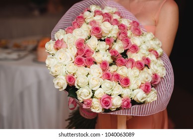 large bouquet of different-colored roses in the hands of a girl