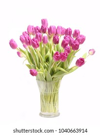 A large bouquet of pink tulips in a glass vase is isolated on a white background.
