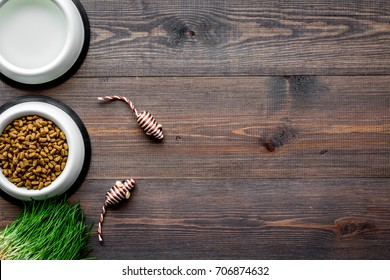 large bowl of pet - cat food with toys on wooden background top view mockup