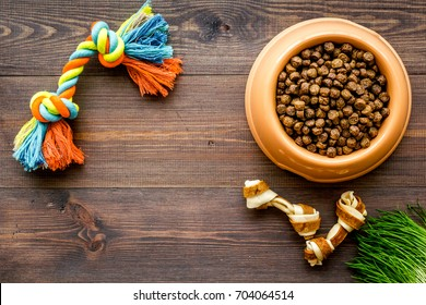 large bowl of pet - dog food with toys on wooden background top view mockup