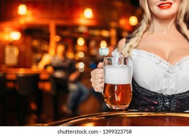 Large breasted waitress  holds mug of fresh beer