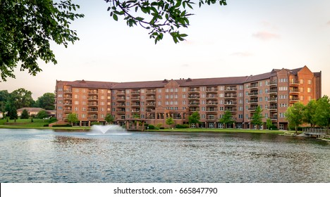 Large brick apartment building in front of a lake at a retirement community