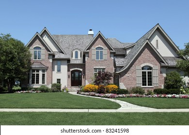 Large brick home with a variety of flowers