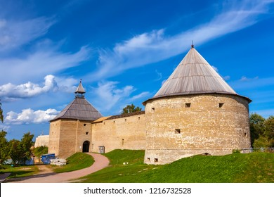 Large brick wall of the old Russian fortress with a round conical wooden roof on the restoration under a clear blue sky at summer day. Staraya Ladoga Fortress, Leningrad Region, Russia.