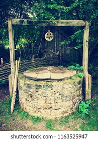 Large brick wishing well, secret garden, wooden pully frame and lid. Wild green plants tangling around the well. Make a wish, fairies and magic.