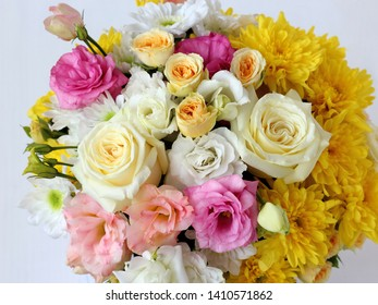 large bright bouquet of fresh flowers: white chrysanthemums, yellow chrysanthemums, yellow roses, pink eustoma, white eustoma, greens, close-up on a white background with a blurred background