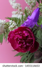 A large bright bouquet of peony flowers, campanula, sorbaria. Bright rich colors, pink background, perfect decoration for a wedding invitation or holiday greetings.