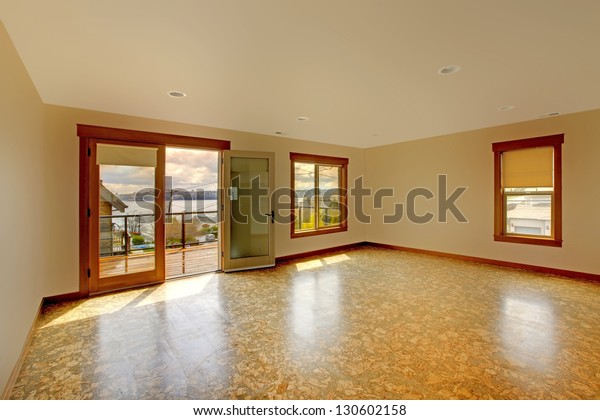 Large bright empty room with cork floor and balcony.New luxury home interior.