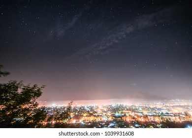a large bright glowing city, many lanterns and lights, under the night starry sky