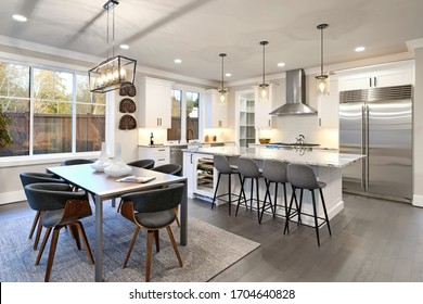 Large bright luxury kitchen interior with large dining room table and island with white marble with dark brown hardwood.