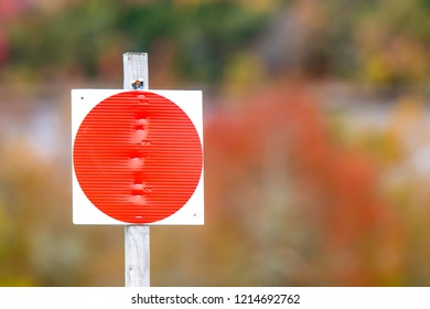 A large bright red dot on a sign attached to a stick. The dot indicates that hunting and trapping are not permitted.