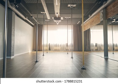 Large bright room with vertical poles for dancing, big mirrors and window with curtains