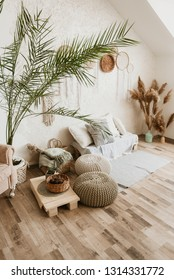 Large bright Scandinavian bedroom with white brick wall and wooden floor. Many plants in pots on the floor.