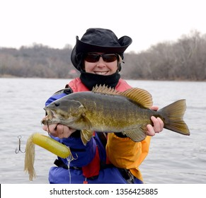 A large brown and bronze smallmouth and a large tube jig bass being held horizontally by a woman in a blue and gold drysuit on a river in winter on a cloudy day