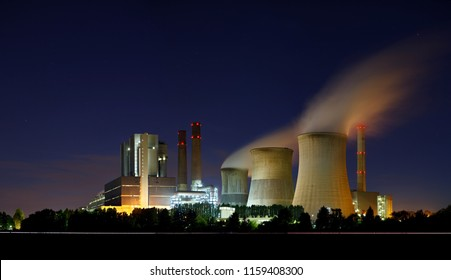 A large brown coal power station with night blue sky and steam.