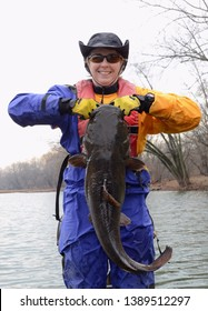 A large brown flathead catfish being held vertically by the jaw by a smiling standing woman in a blue and gold dry suit on a river on a cloudy day in winter.
