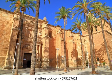Large building of the Cathedral of Almeria (Cathedral of the Incarnation of Almeria) surrounded by tall palm trees, Andalusia, Spain