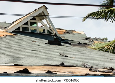 A large building with a damaged roof following a massive supertyphoon / hurricane