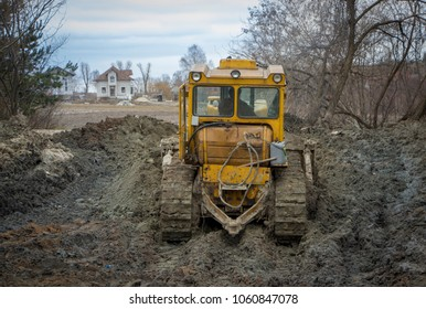 A large bulldozer digs a reclamation channel