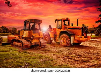 Large bulldozers at construction site, cloudy sky and sunset in background.
