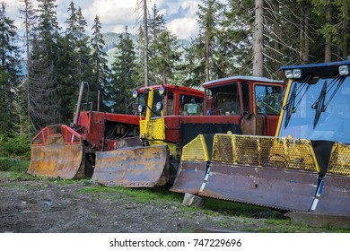 Large bulldozers with snow-plowing buckets stand in a row (Ukraine, Carpathians, Dragobrat)