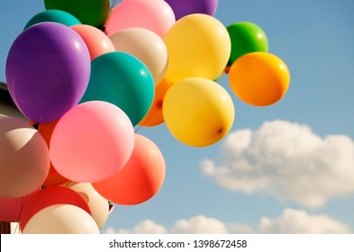 A large bunch of yellow Helium ballons straining on their strings against a sunny sky with white clouds.