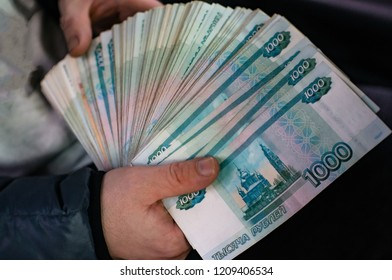 A large bundle of Russian money is squeezed in his hand.